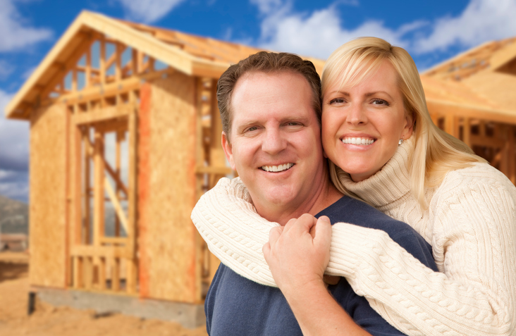 Couple in front of their new home construction